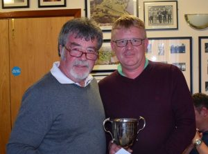 Callum Cunningham receives the McDowell Cup from Jimmy Hamill